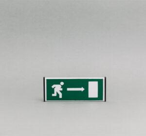 Saugos durų lentelė kuri nurodo išėjimą (vaizdinis).