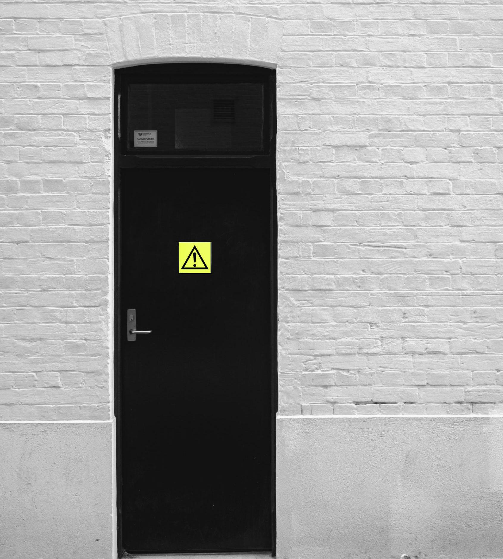 Bendras pavojaus ženklas ant juodų durų