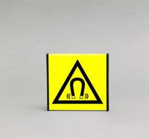 Magnetinio lauko įspėjamasis ženklas, kurio išmatavimai yra 93x93mm, skirtas apie pavojingą magnetinį lauką.